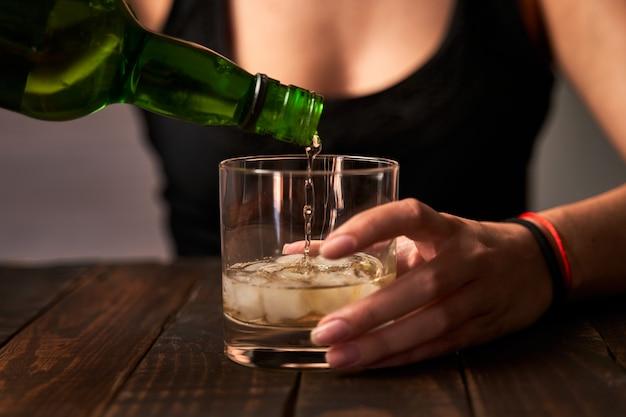 Betrunkene frau, die ein glas alkohol vorbereitet. konzept von alkoholismus und sucht.