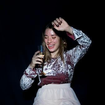 Betrunkene frau, die mit champagnerglas steht