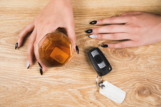 Betrunkene frau mit einem glas whisky und autoschlüssel auf dem tisch
