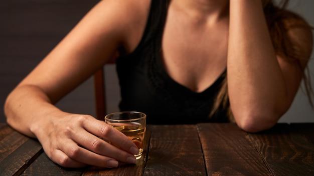 Betrunkene frau trinkt an einer bar. konzept von alkoholismus und alkoholabhängigkeit.