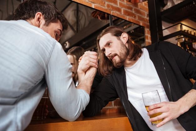 Betrunkene freunde spielen im armdrücken