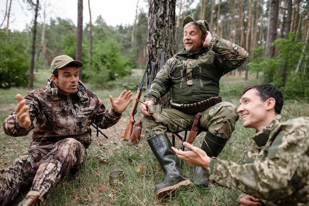 Betrunkene jäger haben ein picknick, das eine lustige geschichte erzählt