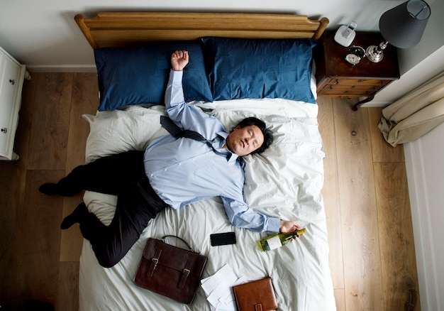 Betrunkener asiatischer geschäftsmann, der einschlafen