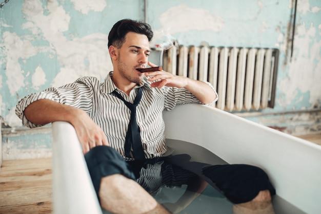 Betrunkener geschäftsmann bankrott in badewanne, selbstmordattentäter