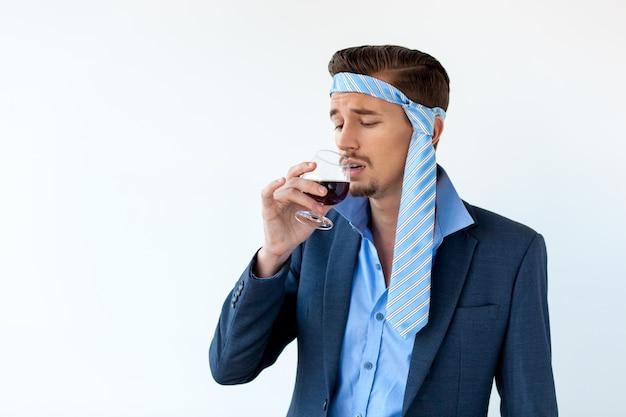Betrunkener geschäftsmann mit kopfschmerzen trinkt rotwein
