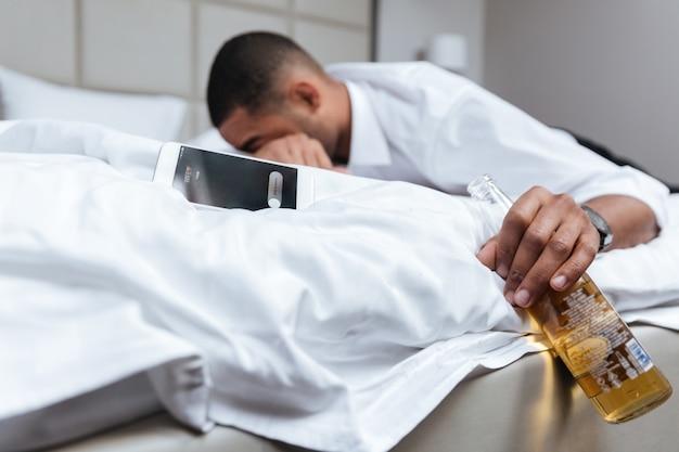Betrunkener junger afrikanischer mann im hemd, der auf bett schläft und flasche bier in der hand hält. flasche im fokus. seitenansicht
