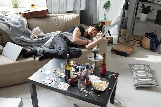Betrunkener junger mann, der auf sofa unter unordentlichem zeug in schmutzigem raum mit alkoholflasche auf tisch schläft