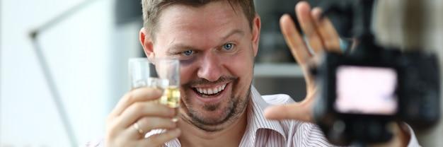 Betrunkener männlicher regisseur hält ein glas mit whisky