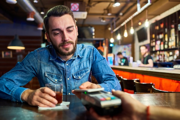 Betrunkener mann, der über nfc im pub zahlt