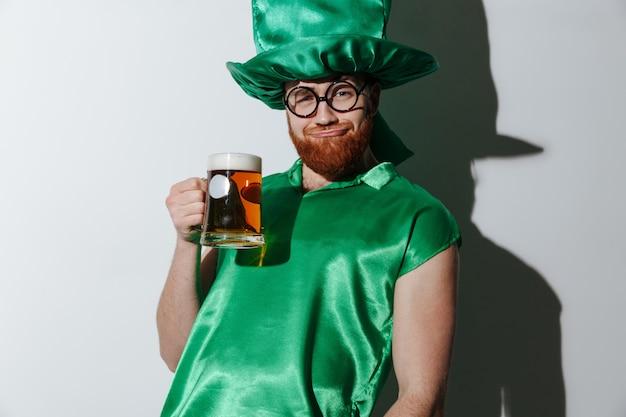 Betrunkener mann in st.patriks kostüm, das bier hält