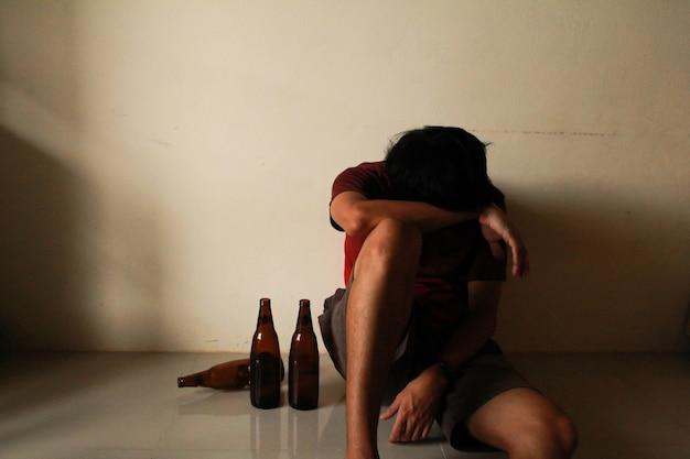 Betrunkener mann mit bierflasche hat stress im leben und sitzt allein in einem leeren raum, traurig, einsam, schule, jugend, häusliche gewalt, ungewollte liebesprobleme, allein, familie