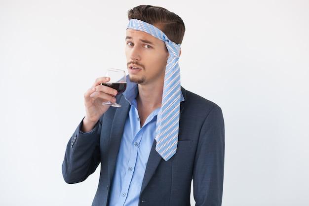 Betrunkener mann mit einem glas wein und krawatte auf kopf