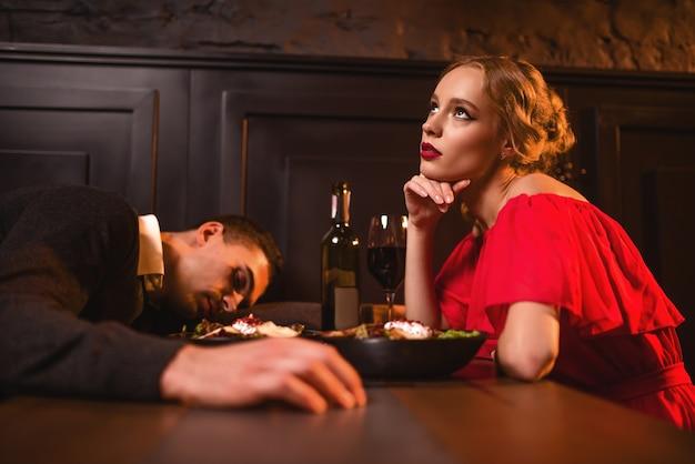 Betrunkener mann schläft am tisch gegen frau im roten kleid im restaurant. paar haben einen verwöhnten abend