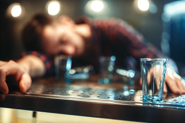 Betrunkener mann schläft an der theke, alkoholabhängigkeit. männliche person in der kneipe, alkoholismus