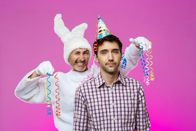 Betrunkener mann und kaninchen bei der geburtstagsfeier über lila wand.