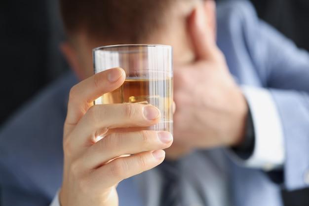 Betrunkener trauriger mann hält glas mit alkoholiker, der an alkoholsuchtkonzept leidet