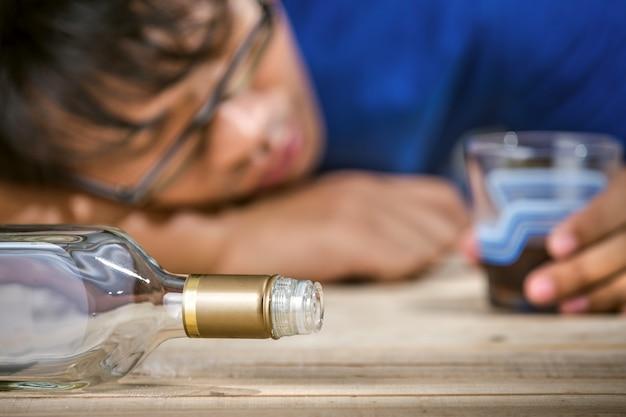 Betrunkener und einsamer lateinischer mann, der eine rum- oder whiskyflasche hält
