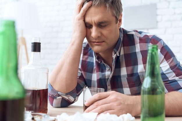 Betrunkener vater sitzt am tisch mit glas