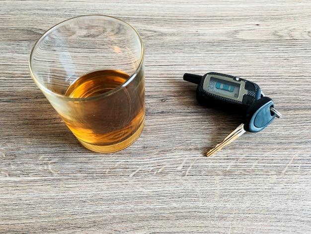 Betrunkenes fahrkonzept. glas mit whisky und autoschlüssel auf dem tisch.
