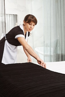 Bett machen ist wie kunst. innenaufnahme eines dienstmädchens in uniform, das beim reinigen der hotelwohnung oder des hauses der eigentümer eine decke auf das bett legt und versucht, staub von allen oberflächen abzuwischen und besten service zu bieten