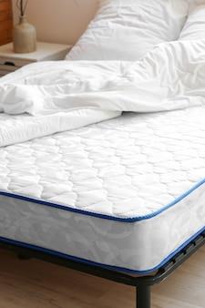 Bett mit bequemer orthopädischer matratze im zimmer