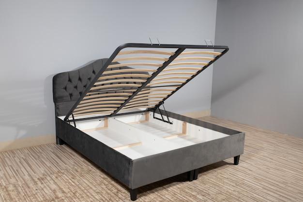 Bett mit grauer polsterung, ohne matratze und mit geöffnetem stauraum in einem leeren raum