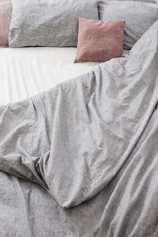 Bett mit grauer und rosa bettwäsche draufsicht