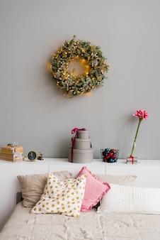 Bett mit kissen und einem weihnachtskranz an der wand mit dekor für weihnachten oder neujahr, innendetails des schlafzimmers im haus