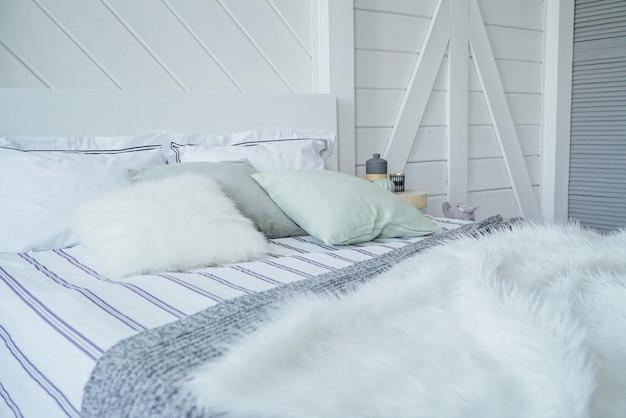 Bett mit kissen und gestrickter pelzdecke im skandinavischen modernen interieur