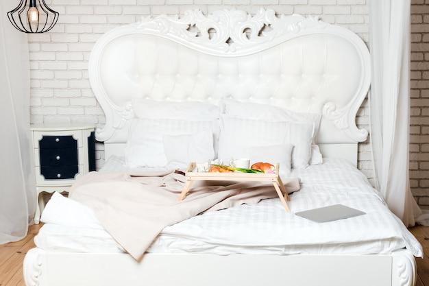 Bett mit laptop und frühstück, freiberufler oder blogger nach hause. arbeit am computer von zu hause aus, morgens und zum frühstück