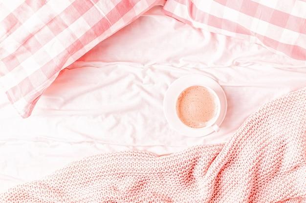 Bett mit rosa gestricktem plaid, kaffee und makronen, draufsicht, kopierraum, flache lage.