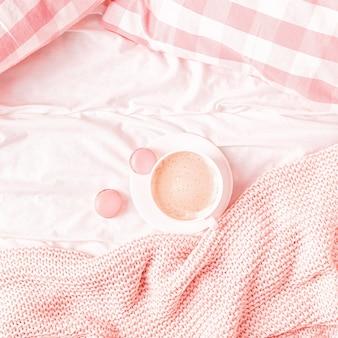 Bett mit rosa gestricktem plaid, kaffee und makronen