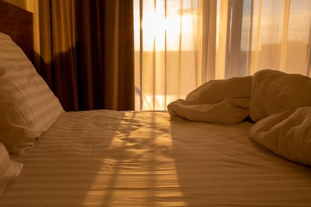 Bett mit weißer bettwäsche bei sonnenaufgangschlafplatz mit kissen und einer decke im morgengraueneinschlafen im bett
