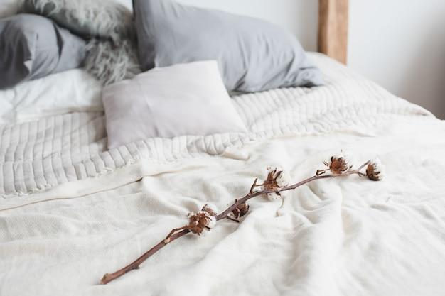 Bett und baumwollblume. gemütliches zu hause.