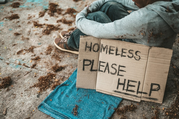 Bettler, die mit obdachlosen nachrichten auf der straße sitzen, helfen bitte.