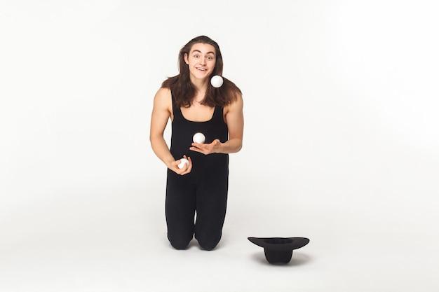 Bettler, frag. jongleur schaut in die kamera und jongliert mit bällen. innenaufnahme