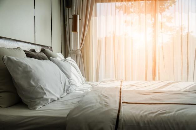 Bettmädchen mit sauberen weißen kissen und bettwäsche im beautycenter