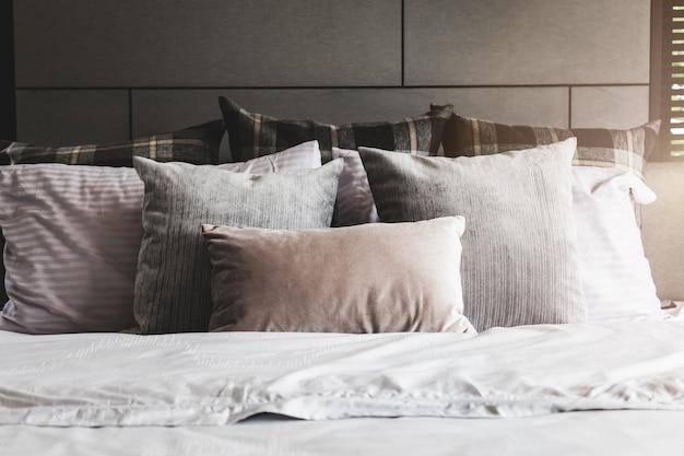 Bettmädchen mit sauberen weißen kissen und bettwäsche im schlafzimmer
