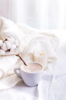 Bettwäsche mit einem flauschigen strickplaid und einer tasse kaffee, baumwollblumen und kerze.
