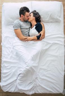 Bettzeit. die familie schläft. schönes junges verliebtes paar liegt auf dem großen weißen bett und ruht sich aus. mann und frau zusammen im bett. draufsichtfoto