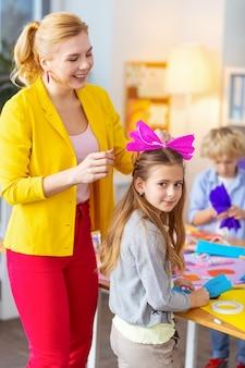 Beuge dich auf dem haar. lächelnde blonde lehrerin, die rosa papierschleife auf das haar ihres süßen schulmädchens legt