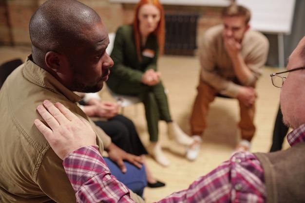 Beunruhigter afrikanischer mann in freizeitkleidung, der einen reifen mann ansieht, der ihn tröstet und ratschläge zur lösung seines problems in einer psychologischen sitzung gibt