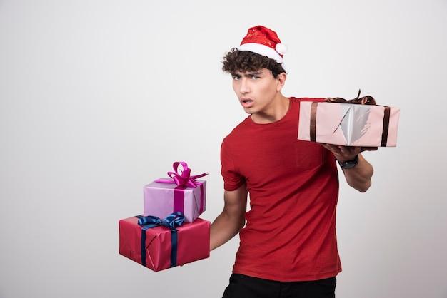 Beunruhigter mann, der seine weihnachtsgeschenke hält