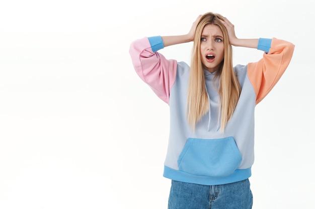 Beunruhigtes und besorgtes, alarmiertes blondes mädchen im hoodie