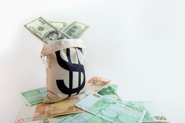 Beutel mit dollarzeichen auf us-dollar- und euro-banknoten