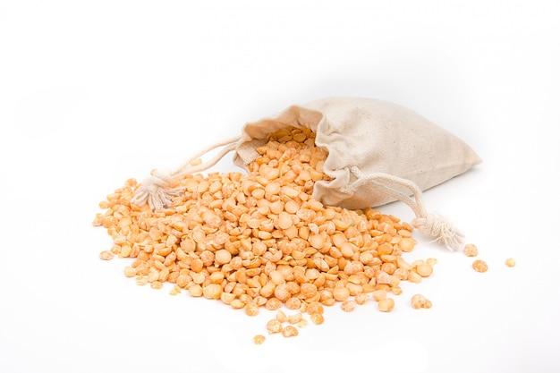 Beutel mit gelben erbsen des getreides auf einem weißen raum.