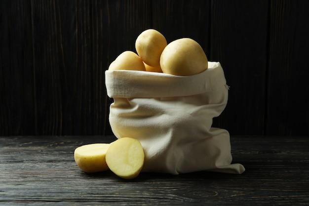 Beutel mit jungen kartoffeln auf holztisch