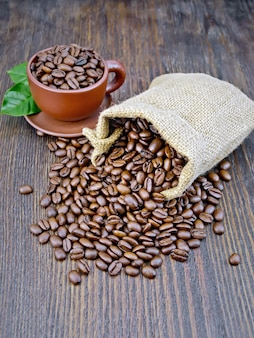 Beutel mit schwarzen kaffeebohnen, braune tasse auf dem hintergrund eines holzbretts