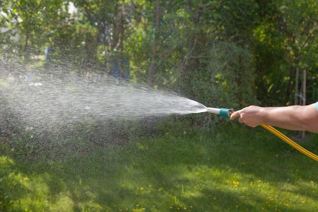 Bewässerung des gartens. schlauch in der hand einer frau.
