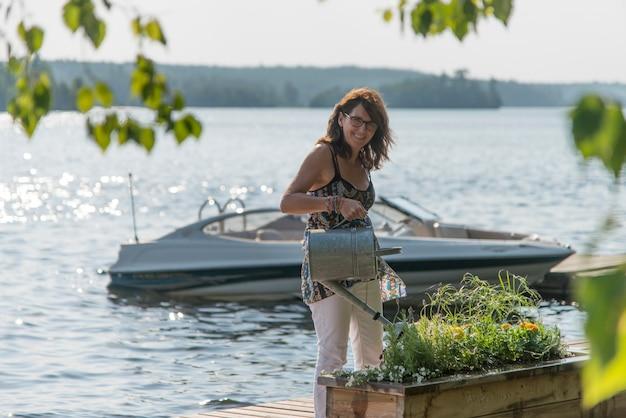 Bewässerungsanlagen der frau auf einem dock, see des holzes, ontario, kanada